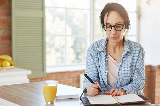Indoor shot of serious european woman holds pen, writes information she found over internet or book in notebook, sits at wooden kitchen table with juice.