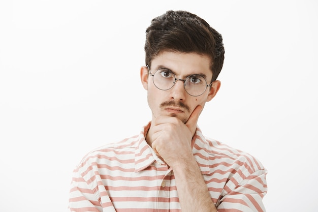 Indoor shot of serious focused angry elder brother with moustache in trendy glasses, holding hand on chin and staring with displeased annoyed expression, solving hard problem over gray wall