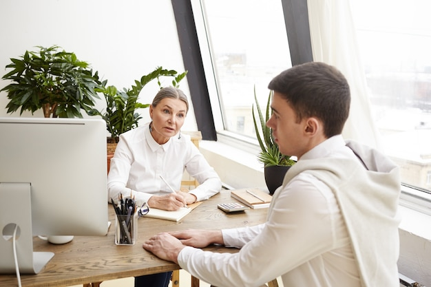 Indoor shot of serious middle aged female human resources specialist in white shirt sitting at her workplace, conducting job interview with promising young male candidate, making notes in her notebook
