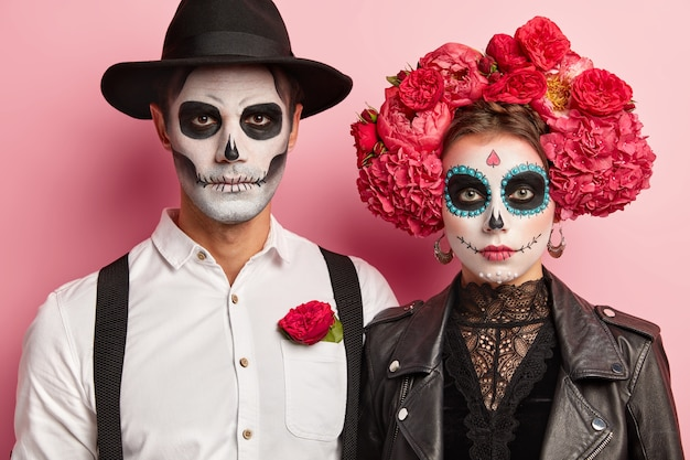 Indoor shot of serious romantic couple pose before halloween event, wear flower wreath and hat on heads, traditional scary costumes, look directly at camera, have zombie makeup in mexican style
