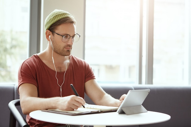 Indoor shot of serious university student in spectacles and hat, writes notes from tablet