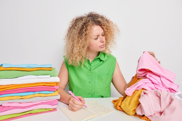 Indoor shot of serious woman examines fabric of clothes writes down meaning of washing symbols finds information about cotton wash sits at table looks attentively at laundry. garment care concept
