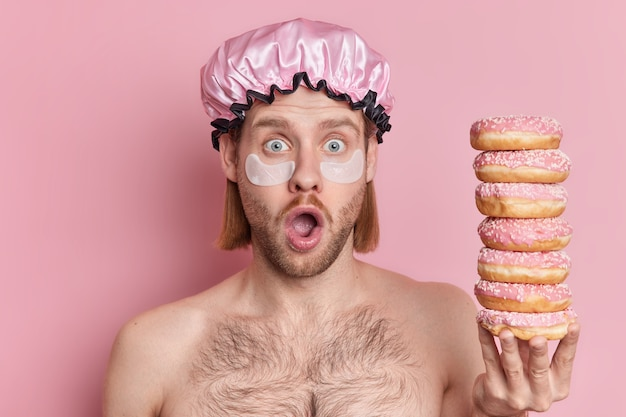 Indoor shot of shocked adult man looks terrified at camera keeps mouth opened applies patches under eyes  holds pile of tasty sweet doughnuts poses naked against pink background