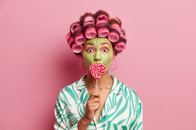 Indoor shot of shocked african american woman applies hair rollers to make perfect hairstyle covers mouth with lollipop makes green nourishing mask to reduce fine lines isolated over pink wall.