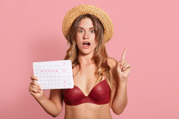Indoor shot of shocked caucasian young female has surprised facial expression, points up with index finger, wearing in red swimsuit and straw hat, holds period calendar, forget date of periods.
