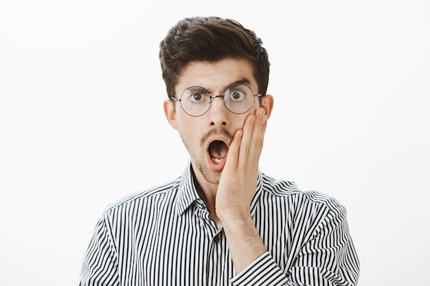 Indoor shot of shocked emotive adult male coworker in glasses, dropping jaw and holding palm on cheek, being surprised and stunned with truthful story of employee, standing amazed over gray wall