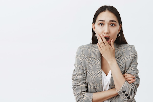 Indoor shot of shocked and excited attractive dark-haired female in trendy jacket, dropping jaw and covering opened mouth, being impressed and surprised, hearing rumor or gossip