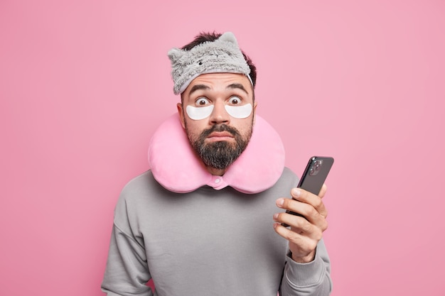 Indoor shot of shocked man checks email box via smartphone stares surprised, wears sleepmask beauty patches to reduce puffiness under eyes after sleeping