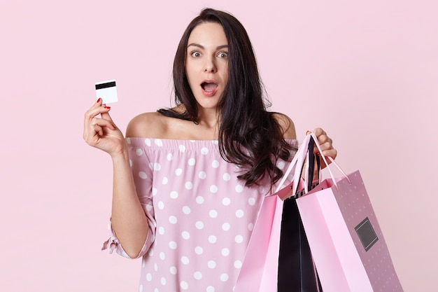 Indoor shot of shocked young european woman with terrified expression, has long straight dark hair, dressed in fashionable clothes, holds credit card and shopping bags, models on pink