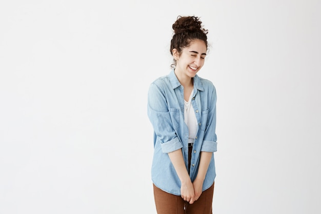 Indoor shot of shy cute student girl with hair bun smiling cheerfully, in denim shirt and brown trousers pleased with present. positive emotions, feelings and face expressions