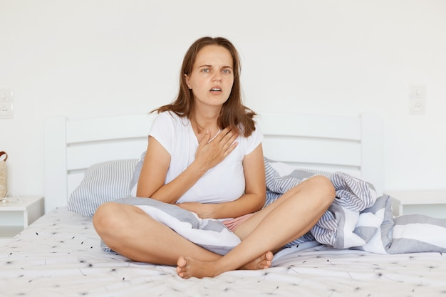 Indoor shot of sick woman wearing white casual t shirt, sitting on bed with crossed legs, touching her chest, suffering from heart pain, looking at camera with frowning face.