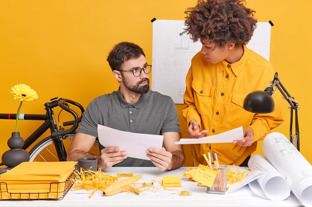 Indoor shot of skilled students analyze exam mistakes pose at office desk do homework in coworking space discuss something. two woman and man coworkers collaborate on making project make drafts