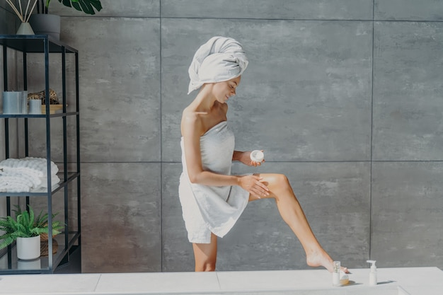 Indoor shot of slim female model applies leg cream stands wrapped in bath towel takes care of body and skin undergoes beauty treatments after taking shower poses in bathroom. cosmetology concept
