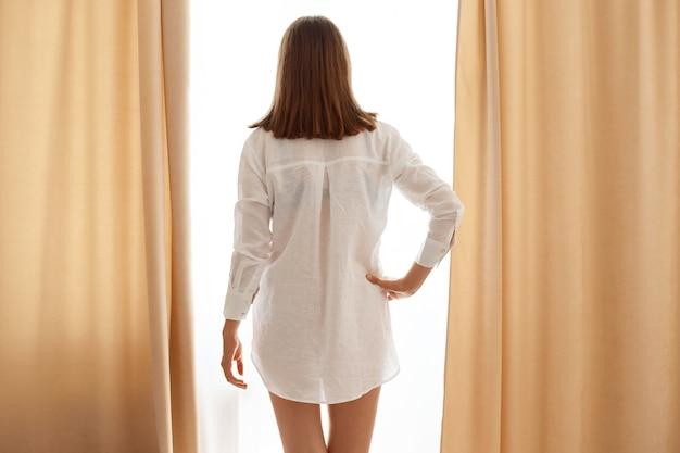 Colpo al coperto di donna magra con i capelli scuri in posa all'indietro, tenendo la mano sui fianchi, guardando la finestra, indossando una camicia di cotone bianca, in piedi vicino a tende beige.