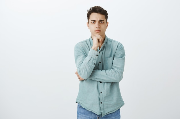 Indoor shot of smart focused troubled guy with short black hair in casual outfit