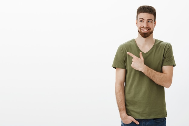 Indoor shot of smart handsome bearded caucasian guy in good mood happy smiling delighted as looking and pointing at upper left corner having great plan pleased against white wall