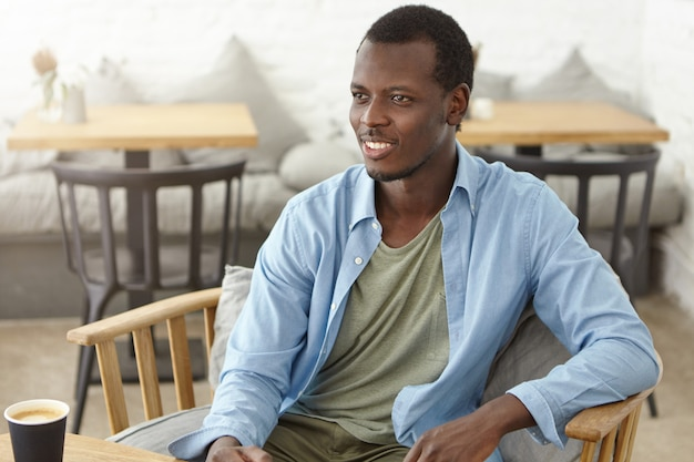 Indoor shot of smiling black unshaven male in shirt, sitting at wooden chair at cafe, drinking hot coffee or cappuccino, looking at someone with smile, while having pleasant talk with friend