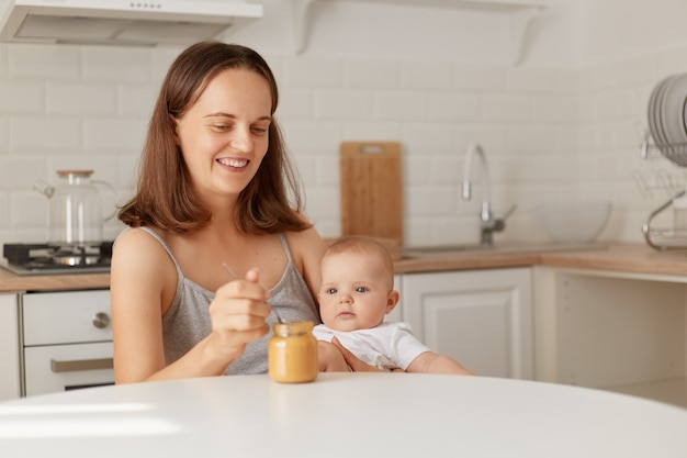 Indoor shot of smiling female sitting at table in kitchen with baby girl in hands and feeding daughter with fruit or vegetable puree, complementary feeding of a child.