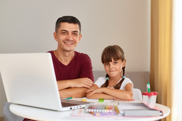 Indoor shot of smiling handsome man sitting at table with his little daughter in front of laptop, looking at camera with happy expression, distant education.
