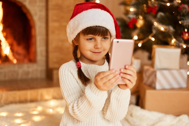 Indoor shot of smiling happy female child holding smartphone in hands, wearing white sweater and santa claus hat, sitting on floor near christmas tree, present boxes and fireplace.