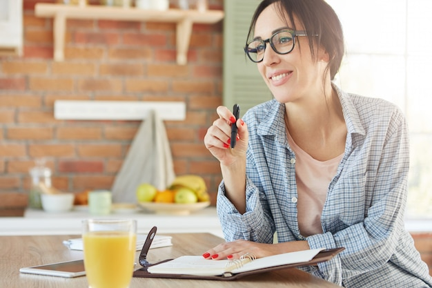 Indoor shot of smiling happy woman sits at kitchen table, makes notes in diary, plans what to do,