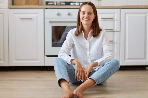 Indoor shot of smiling woman with dark hair wearing white shirt and jeans sitting on the floor in light room against kitchen set, looking at camera with positive expression.