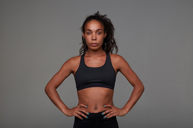 Indoor shot of sporty young dark skinned curly brunette female with casual hairstyle keeping her hands on waist while looking with calm face, isolated