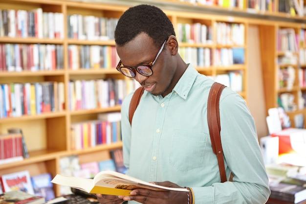 Indoor shot of student in glasses looking through book in his hands