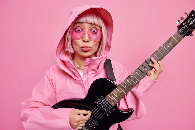 Indoor shot of stylish asian hipster girl looks surprisingly through trendy pink sunglasses wears jacket with hood plays favorite melody on acoustic guitar demonstrates her abilities and talents
