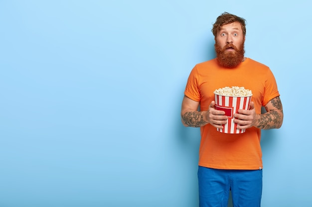 Indoor shot of surprised bearded redhead man eats popcorn