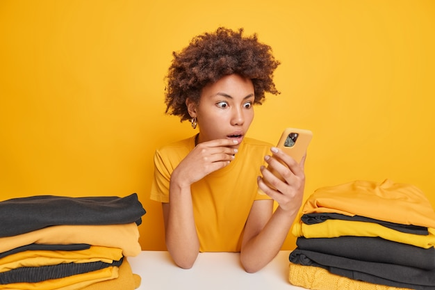 Indoor shot of surprised curly haired afro american woman stares at smartphone display sits at table with two piles of neatly folded washed laundry isolated over yellow
