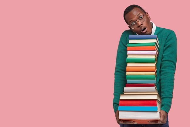 Indoor shot of surprised dark skinned man in eyewear carries heavy stack of textbooks, tilts head