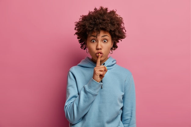 Indoor shot of surprised dark skinned woman has secret plan, makes silence gesture, looks with stupefied expression, wears blue hoodie, shows shush or hush sign, poses indoor over rosy wall.