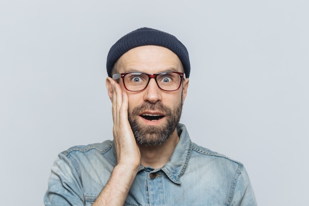 Indoor shot of surprised handsome man, keeps hand on cheek, wears glasses and stylish clothing