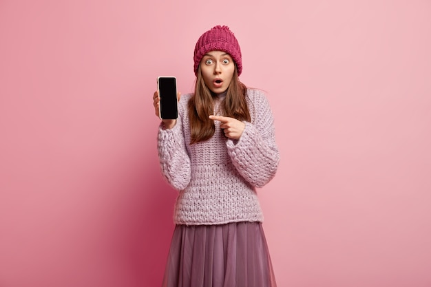 Indoor shot of surprised millenial girl shows you smartphone display, promots nice photo edit application