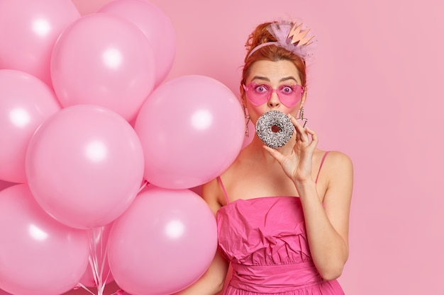 Indoor shot of surprised redhead young woman covers mouth with glazed doughnut