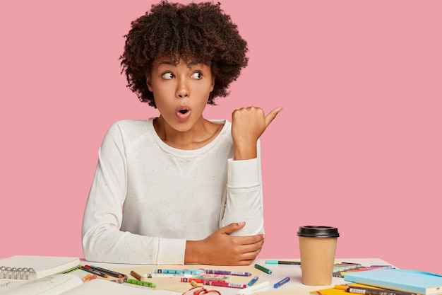 Tiro al coperto di donna scioccata sorpresa ha un'espressione facciale stupefatta, si siede alla scrivania con il necessario fermo, beve bevande fresche, punta allo spazio libero con il pollice, nota qualcosa di orribile