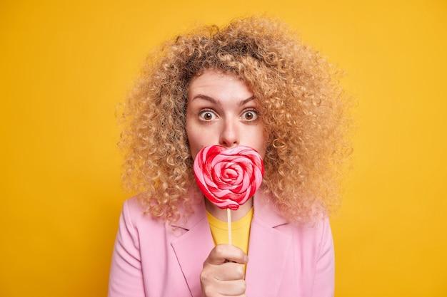 La foto in interni di una donna sorpresa tiene la caramella a forma di cuore sulla bocca