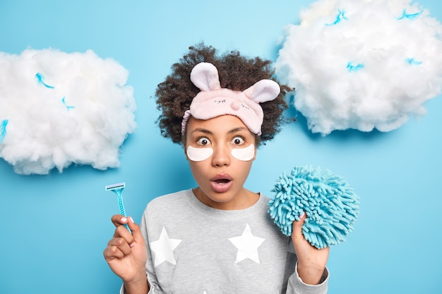 Indoor shot of surprised young afro american woman with curly bushy hair holds razor for depilation bath sponge undergoes beauty and hygiene procedures at home after awakening in morning poses indoor
