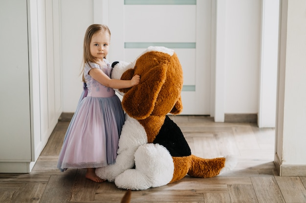Indoor shot of sweet little blonde haired girl hugging her large soft dog toy, looking at camera with serious facial expression, standing at hall, playing at home in the morning.