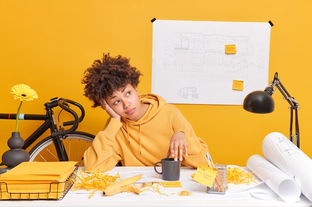 Indoor shot of thoughtful afro american student prepares for exams dreams about holidays and rest poses at dekstop with papers stickers sketches dressed in casual yellow sweatshirt has design courses