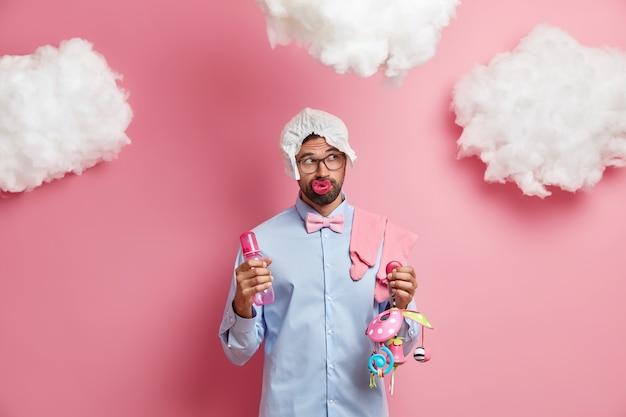 Colpo al coperto di premuroso futuro padre barbuto posa con oggetti per bambini indossa occhiali camicia e pannolino sulla testa pensa al nome per il neonato