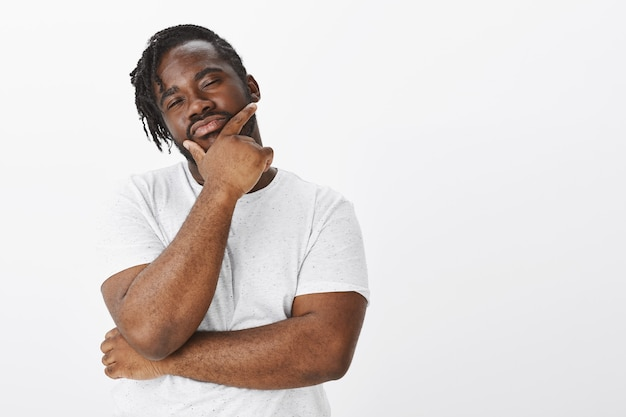 Indoor shot of thoughtful guy with braids posing against the white wall