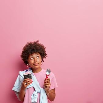 Tiro al coperto di una ragazza millenaria premurosa guarda sopra, concentrato verso l'alto, detiene un delizioso gelato freddo e un cucchiaio per mangiare, indossa una maglietta e un maglione legati sulla spalla, gode del gusto del dessert