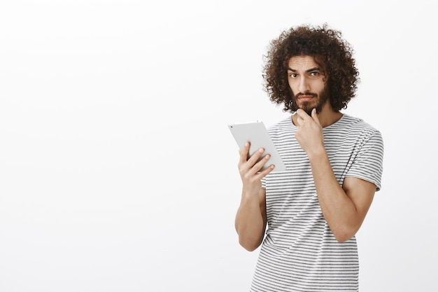 Indoor shot of thoughtful serious handsome guy with curly hair, touching beard and looking focused while thinking, holding white digital tablet