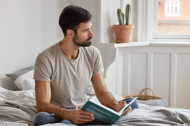 Indoor shot of thoughtful unshaven man reads books, learns some tips for successful project, sits at bed, dressed in casual clothing, focused aside, has dark stubble. leisure and literature concept