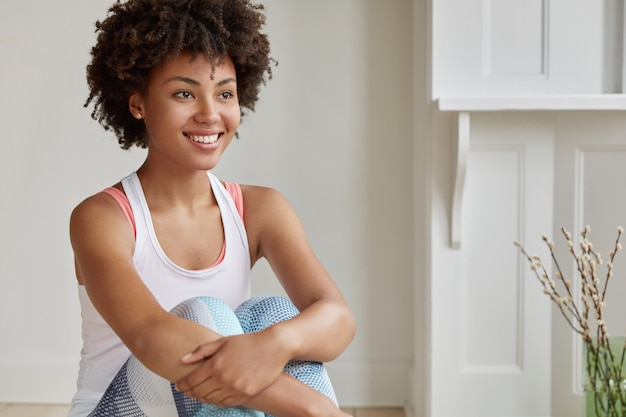 Indoor shot of thoughtful woman with afro haircut, has toothy smile, looks into distance, has rest after gymnastic exercises