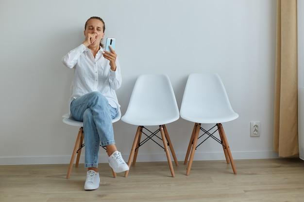 Ripresa al coperto di una donna stanca e annoiata seduta in coda su una sedia contro il muro chiaro, indossando abiti in stile casual, coprendo la bocca mentre sbadiglia, usando il telefono mentre si aspetta molto tempo.
