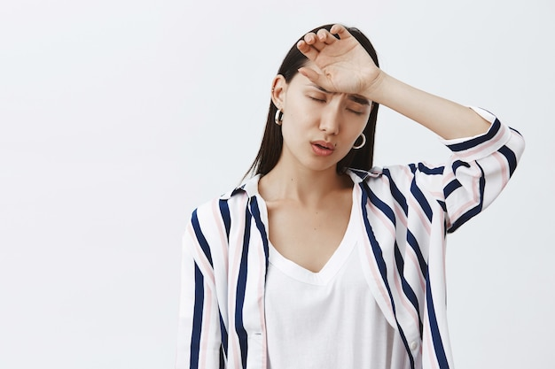 Indoor shot of tired and gloomy cute woman in striped trendy blouse, holding arm on forehead and breathing out, having headache