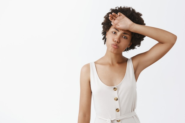 Indoor shot of tired gloomy good-looking female entrepreneur in white overalls with afro hairstyle whiping sweat out of forehead pursing lips and tilting head wanting rest after hard work